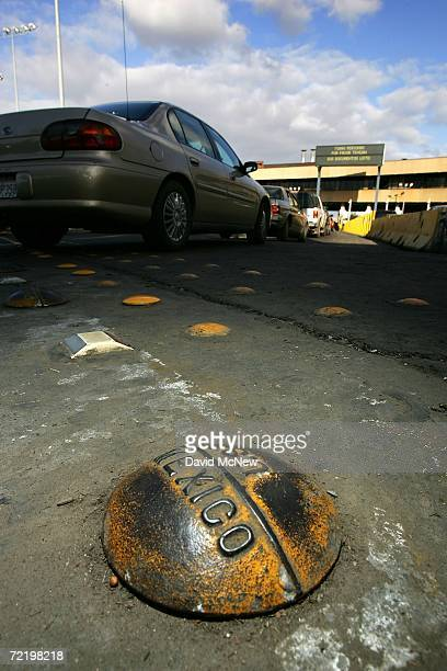 Cars pass an international border marker as they wait in typically long lines to enter the United States from Mexico on the morning that the US...