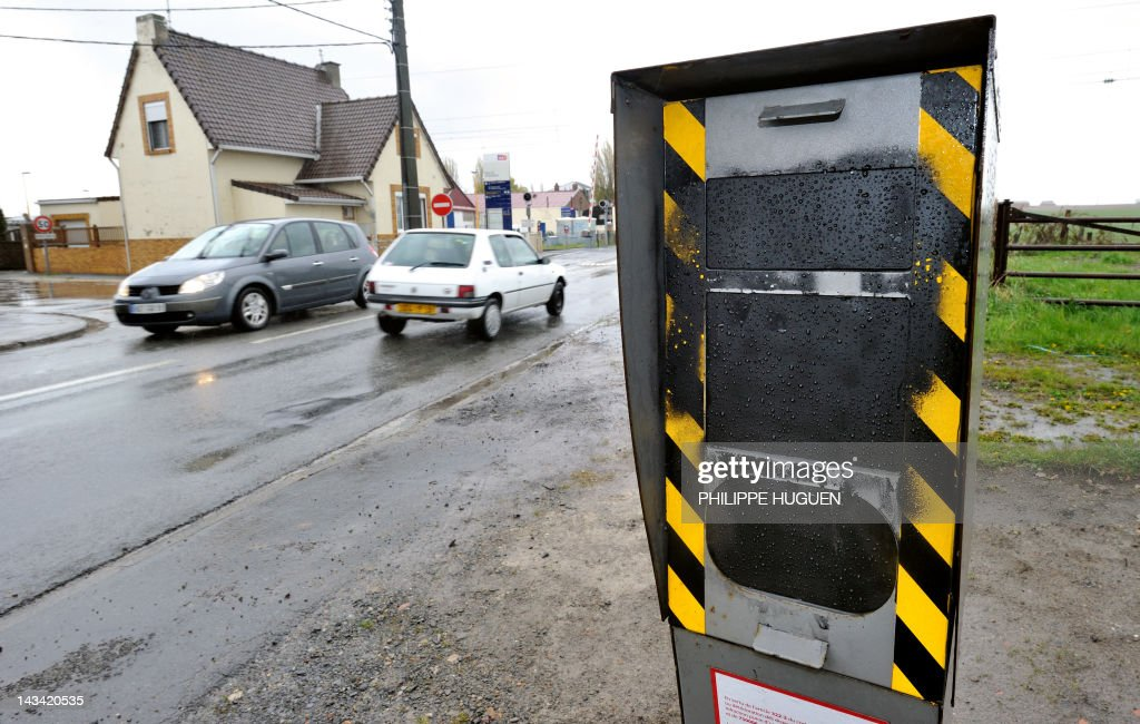 Cars pass by a speed radar (GPS) covered with black paint on a Strazeele's road, northern France on April 23, 2012.