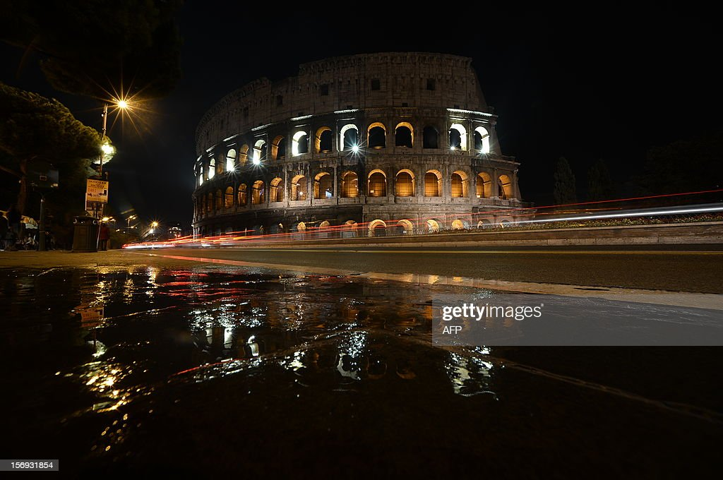 Cars pass by the Colosseum illuminated on November 25, 2012 in Rome on the occasion of the International Day for the Elimination of Violence against Women. AFP PHOTO / FILIPPO MONTEFORTE