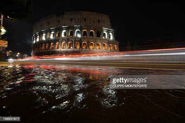 Cars pass by the Colosseum illuminated on November 25 2012 in Rome on the occasion of the International Day for the Elimination of Violence against...