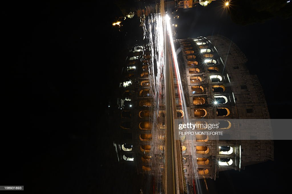 Cars pass by the Colosseum illuminated on November 25, 2012 in Rome on the occasion of the International Day for the Elimination of Violence against Women.