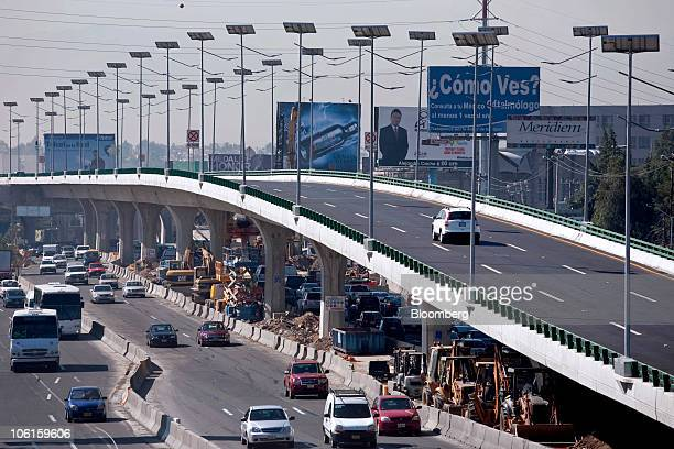 Cars pass under an OHL construction project on the Viaducto Elevado Bicentenario highway north of Mexico City Mexico on Monday Oct 25 2010 OHL...