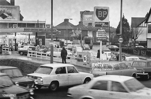 Cars queuing at a petrol station on Woodford Avenue London during a petrol shortage December 1973