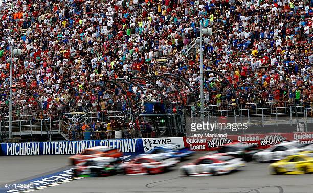 Cars race during the NASCAR Sprint Cup Series Quicken Loans 400 at Michigan International Speedway on June 14 2015 in Brooklyn Michigan