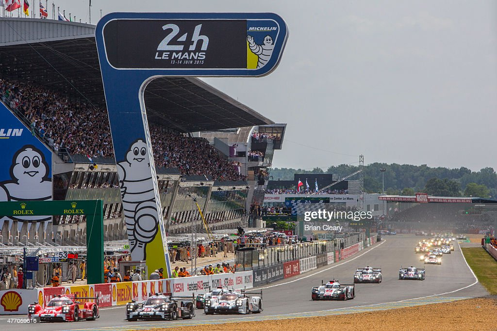 Cars race into the first turn at the start of the 24 Hour of Lemans on June 13 2015 in Le Mans France