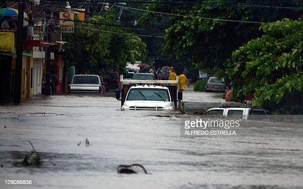 Cars remain stranded in a flooded street in Manzanillo Colima State Mexico on October 12 2011 Jova lost its hurricane status but remained a deadly...