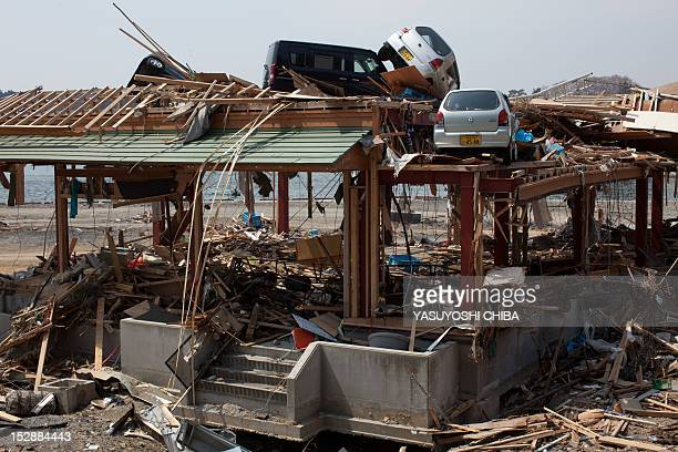 Cars rest on a roof of a tsunami devasted building near the seashore in Kesennuma city Miyagi prefecture on April 14 2011 Japan's seismologists were...