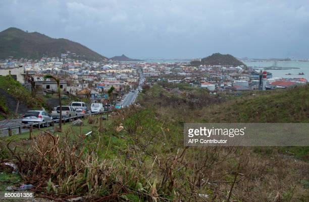 Cars ride in on September 20 in Marigot on the French side of the Caribbean island of SaintMartin after hurricane Maria and Hurricane Irma hit the...