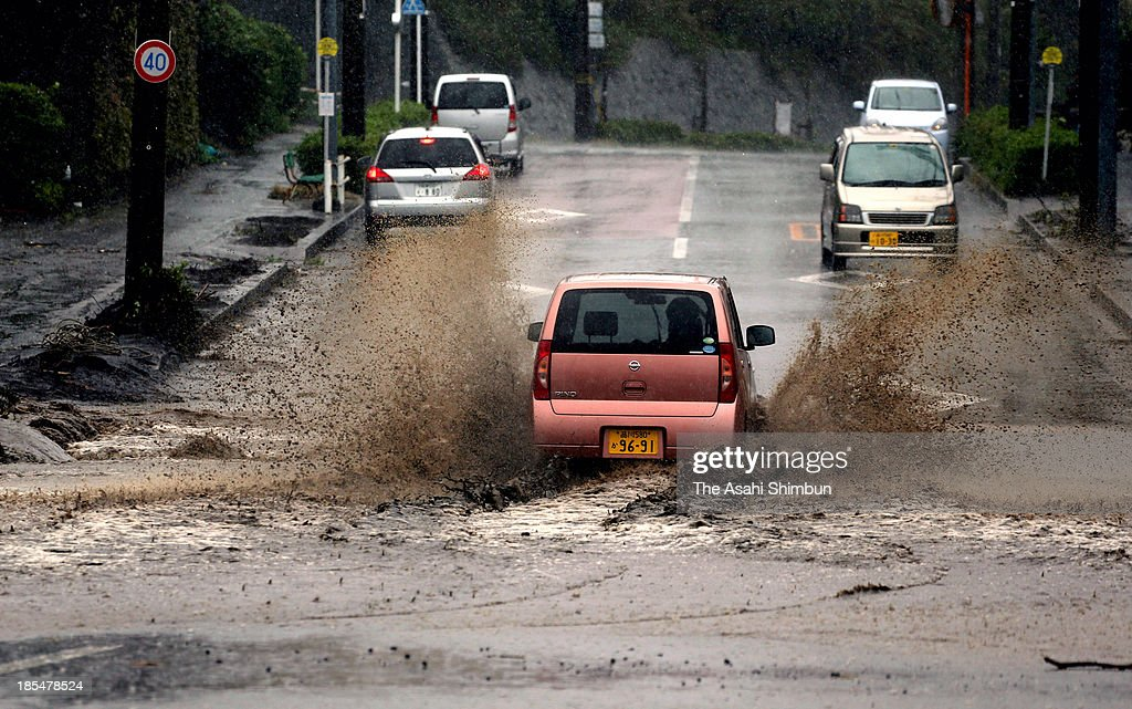 Cars run on the flooded road on October 20, 2013 in Oshima, Tokyo, Japan. The evacuation advisory was issued October 19 as another heavy rain was expected at a landslide devastated Oshima Island. The early morning downpours from Typhoon Wipha, or No. 26 on October 16 caused landslides that covered 1.14 million square meters and damaged or destroyed 283 homes, according to estimates by Oshima town officials.