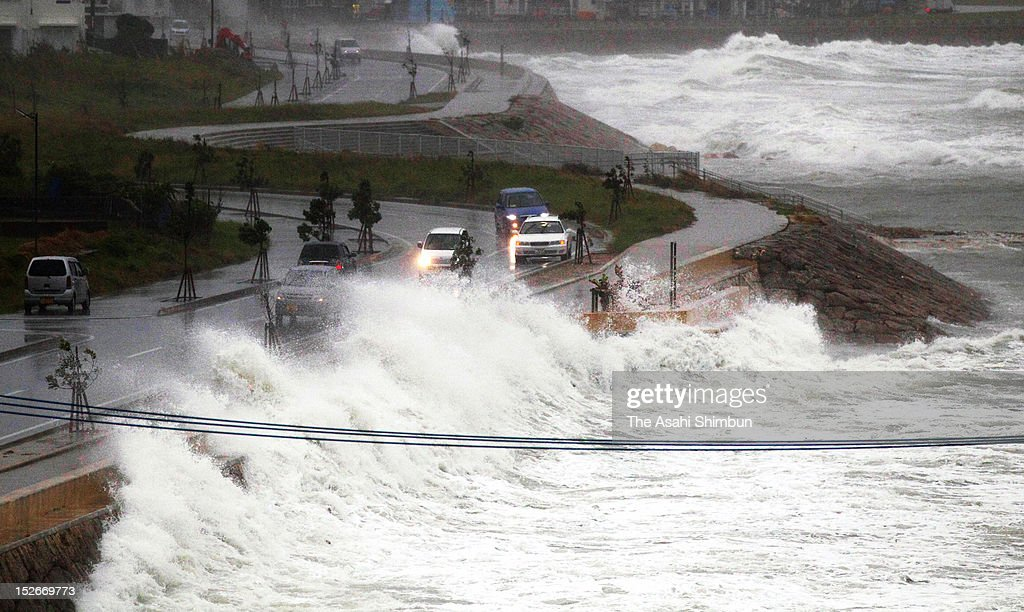 Cars run the flooded road as the high tide triggered by Typhoon Sanba on September 15, 2012 in Yonabaru, Okinawa, Japan.