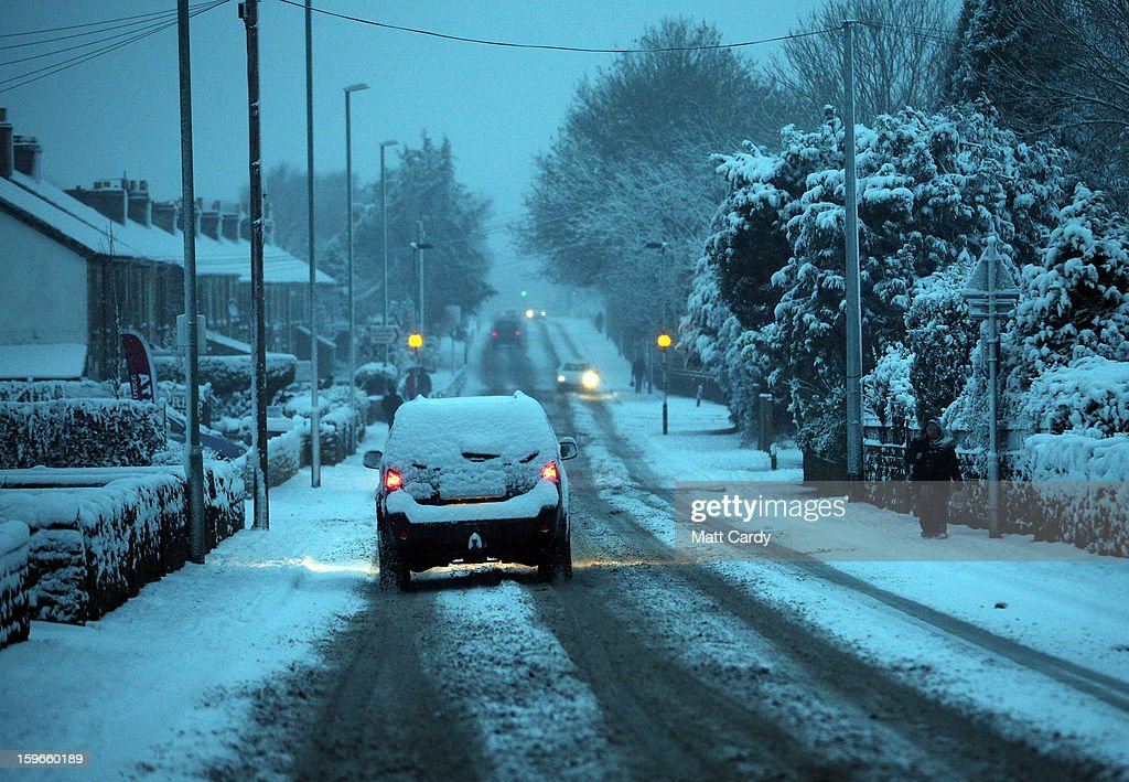 Cars set out in the early morning light in Radstock on January 18, 2013 near Bath, England. Heavy snow is bringing widespread disruption to many parts of the UK.