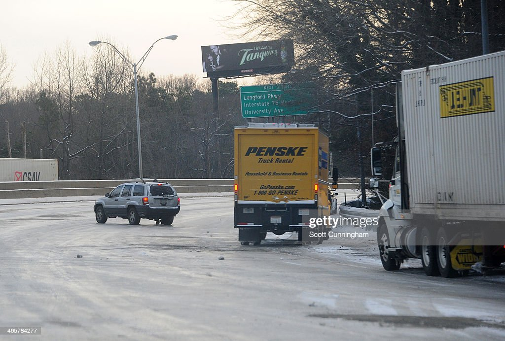 Cars sit along the side of along Interstate 75 in icy conditions January 29, 2014 in Atlanta, Georgia. Thousands of motorists were stranded, many overnight, as a winter storm dropped three inches of snow, and ice made driving hazardous.