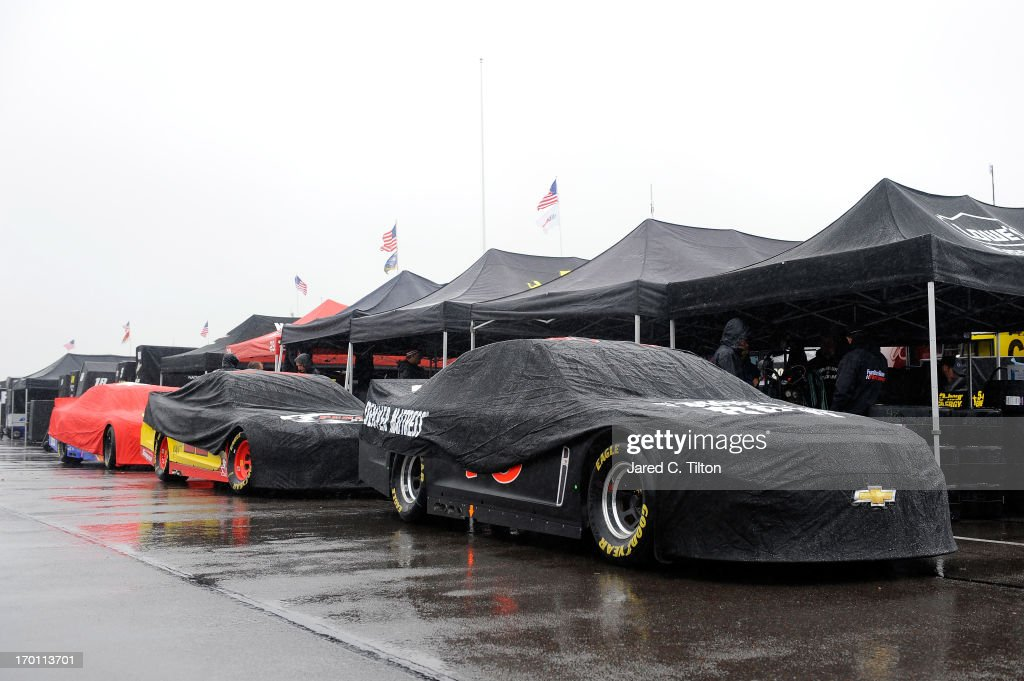 Cars sit covered in the garage area during a rain delay at Pocono Raceway on June 7, 2013 in Long Pond, Pennsylvania.