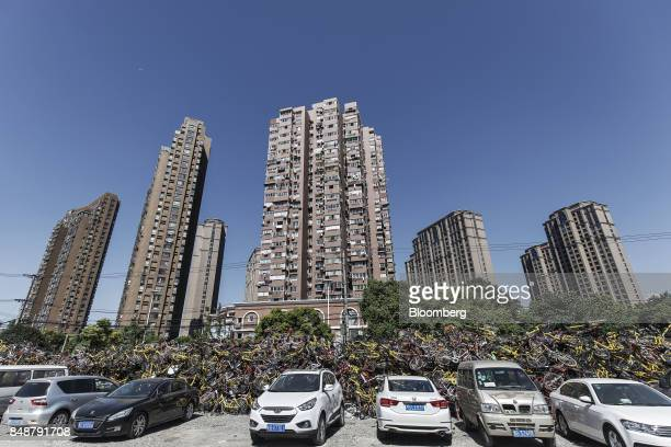 Cars sit parked in front of a pile of ridesharing bicycles in Shanghai China on Thursday Sept 12 2017 Across Chinese cities sidewalks are filling up...