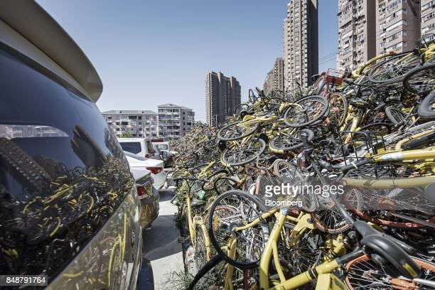 Cars sit parked next to a pile of ridesharing bicycles in Shanghai China on Thursday Sept 12 2017 Across Chinese cities sidewalks are filling up with...