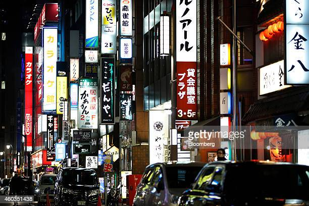 Cars sit parked under illuminated neon signs in Tokyo Japan on Thursday Dec 11 2014 Japanese stocks rose ahead of national elections this weekend...