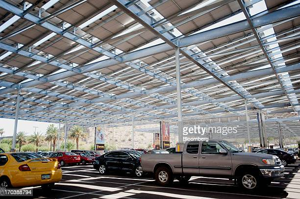 Cars sit parked under solar panels in a parking lot at Arizona State University in Tempe Arizona US on Tuesday June 11 2013 Solar installations in...