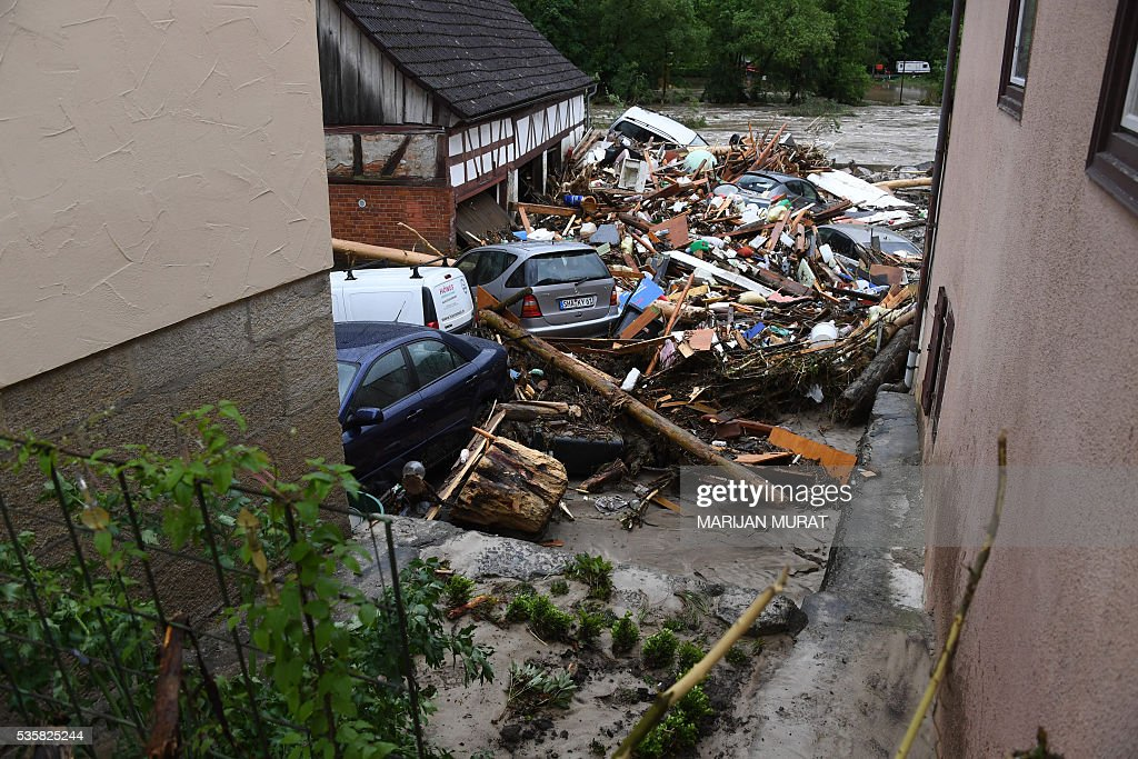 Cars stand amidst of rubbish in a flooded street in Braunsbach, southern Germany, on May 30, 2016. Four people died and several more were injured in southern Germany after violent storms with torrential rains caused severe flooding, authorities said. / AFP / dpa / Marijan Murat / Germany OUT