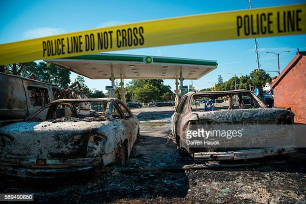 Cars stand burned in the lot of the BP gas station after rioters clashed with the Milwaukee Police Department protesting an officer involved killing...