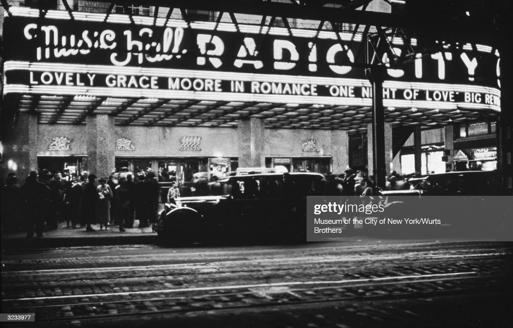 Cars stand in front of a crowded Radio City Music Hall, with a marquee advertising Gracie Moore in the film, 'One Night of Love,' New York City.