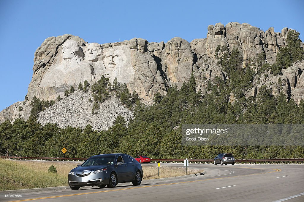 Cars travel along the highway near the entrance to Mount Rushmore National Memorial on October 1, 2013 in Keystone, South Dakota. Mount Rushmore and all other national parks were closed today after congress failed to pass a temporary funding bill, forcing about 800,000 federal workers off the job. A bulletin issued by the Department of Interior states, 'Effective immediately upon a lapse in appropriations, the National Park Service will take all necessary steps to close and secure national park facilities and grounds in order to suspend all activities ...Day use visitors will be instructed to leave the park immediately...'