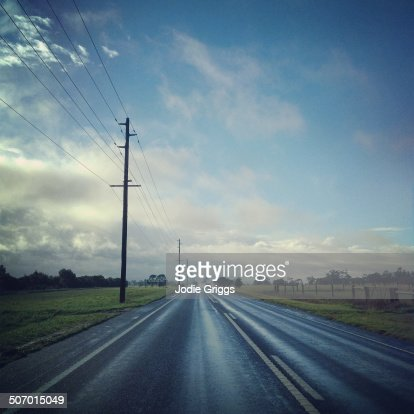 Cars travelling down a straight road after rain