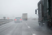 cars, trucks and a rescue vehicle driving in dangerous winter weather with poor visibility during snow and rain on the highway, concept for safety in traffic, copy space