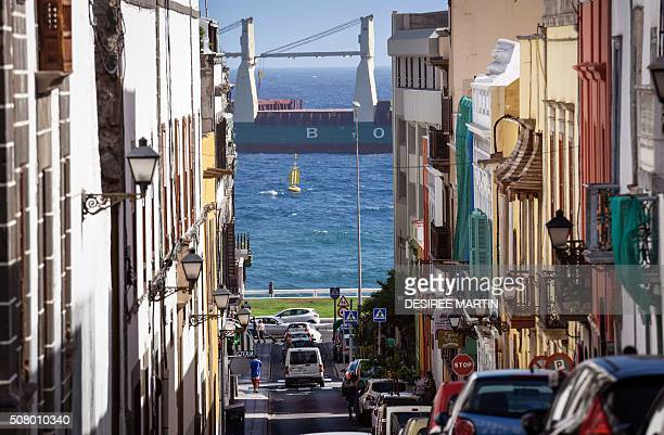 Cars wait at a junction in a street of Vegueta neighborhood of Las Palmas de Gran Canaria with the port in background on January 30 2016 AFP PHOTO/...