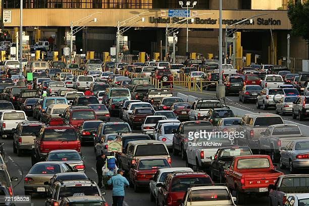 Cars wait in typically long lines to enter the United States from Mexico on the morning that the US population hit the historic milestone of 300...