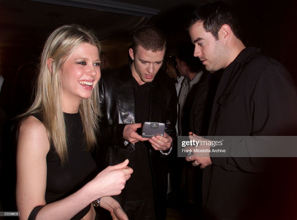 Carson Daly and Justin Timberlake of 'NSYNC trade info on their 2 way pagers as Tara Reid looks on at the 26th Annual Clive Davis PreGrammy Party at...