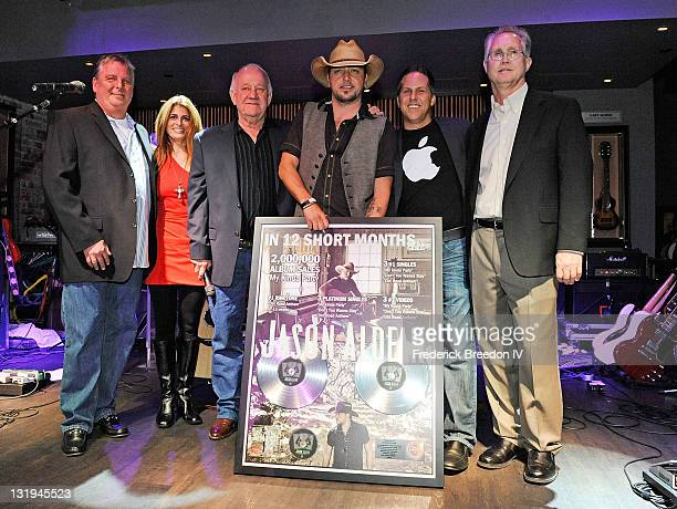 Carson James Leigh Adams Denny Brown Jason Aldean Jon Loba and Rick Shedd pose with Aldeans double platinum plaque at the Broken Bow/Stoney Creek...