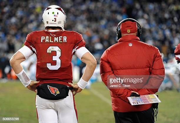 Carson Palmer and head coach Bruce Arians of the Arizona Cardinals look on during the NFC Championship Game against the Carolina Panthers at Bank of...