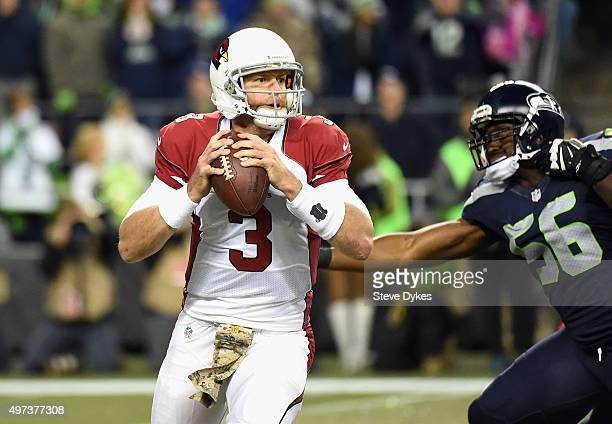 Carson Palmer of the Arizona Cardinals looks to pass as he is pressured by Cliff Avril of the Seattle Seahawks during the first half of their game at...