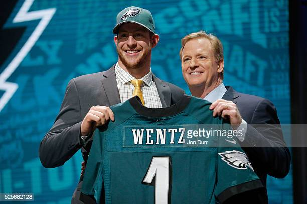 Carson Wentz of the North Dakota State Bison holds up a jersey with NFL Commissioner Roger Goodell after being picked overall by the Philadelphia...