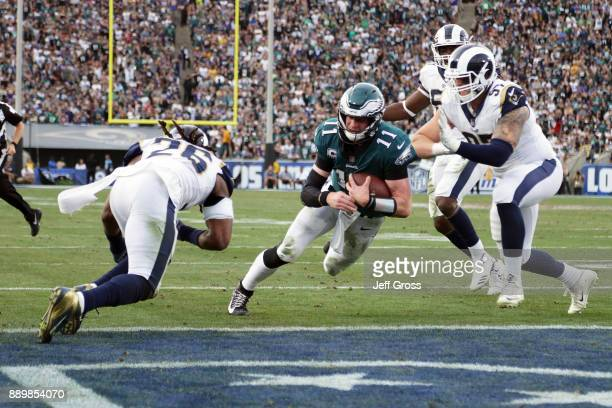 Carson Wentz of the Philadelphia Eagles is hit by Mark Barron of the Los Angeles Rams during the third quarter of the game Wentz was later escorted...