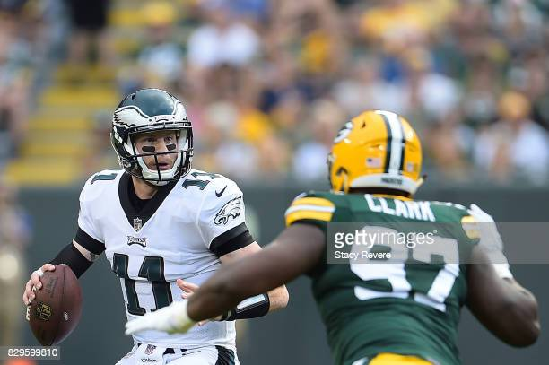 Carson Wentz of the Philadelphia Eagles is pursued by Kenny Clark of the Green Bay Packers during the first quarter of a preseason game at Lambeau...
