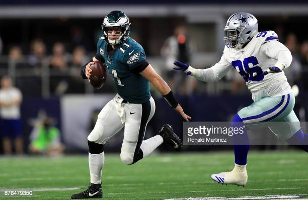 Carson Wentz of the Philadelphia Eagles runs past Maliek Collins of the Dallas Cowboys in the first half at ATT Stadium on November 19 2017 in...