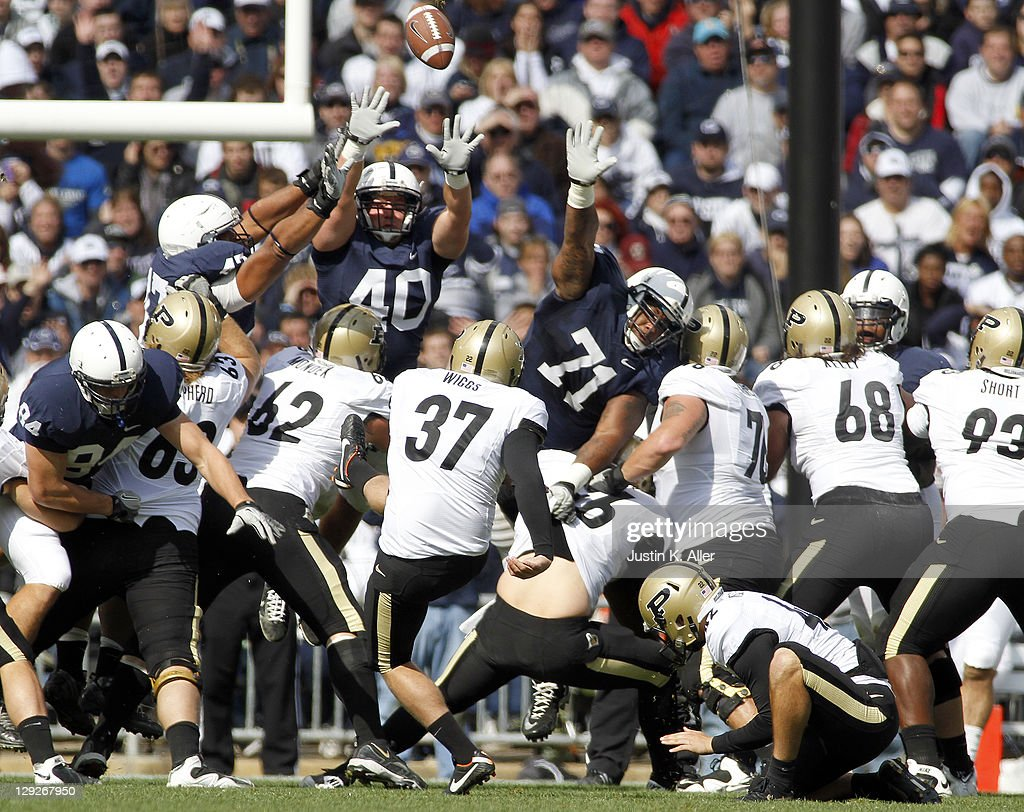 Carson Wiggs of the Purdue Boilermakers kicks a field goal as Glenn Carson and Devon Still of the Penn State Nittany Lions attempt to make a block...