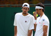 Carsten Ball of Australia speaks with teammate Thomasz Bellucci of Brazil during his gentlemen's doubles first round match against Daniele Bracciali...