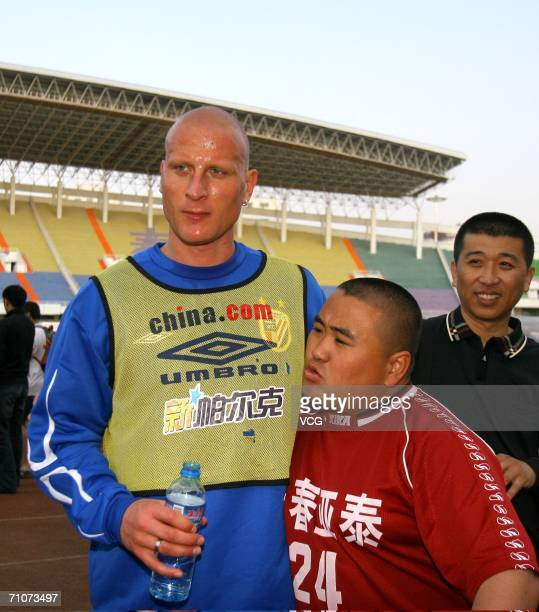 Carsten Jancker stands for a photo with a fan during a training session with Shanghai Shenhua on May 27 2006 in Changchun Jilin province China