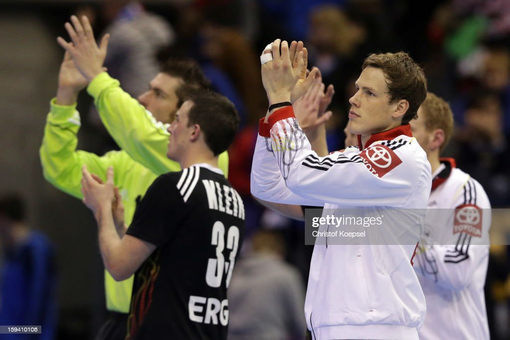 Carsten Lichtlein, Dominik Klein and Sven-Soeren Christophersen of Germany look dejected after the premilary group A match between Tunisia and Germany at Palacio de Deportes de Granollers on January 13, 2013 in Granollers, Spain. The match between Tunisia and Germany ended 25-23.