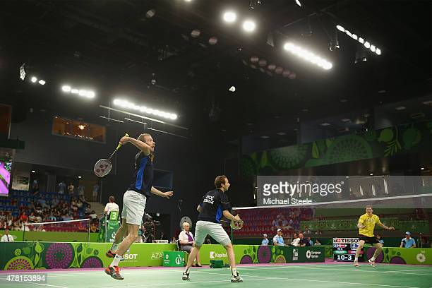 Carsten Mogensen of Denmark sleaps to smash a return as Mathias Boe looks on during the Men's Doubles Group A match against Pavel Florian and Ondrej...