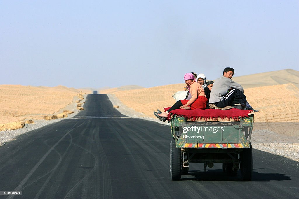 A cart full of Chinese Uygurs drives on a nearly finished section of the second desert highway in the Taklamakan desert near Hetian Xinjiang province...