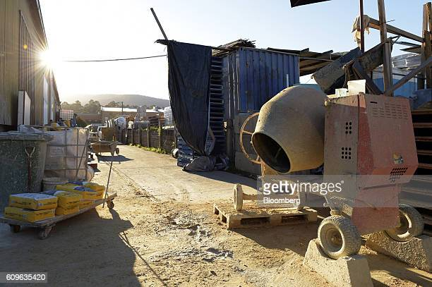 A cart loaded with bags of cement sit next to a concrete mixer at the yard of Gully Concrete supplies in Melbourne Australia on Tuesday Aug 16 2016...