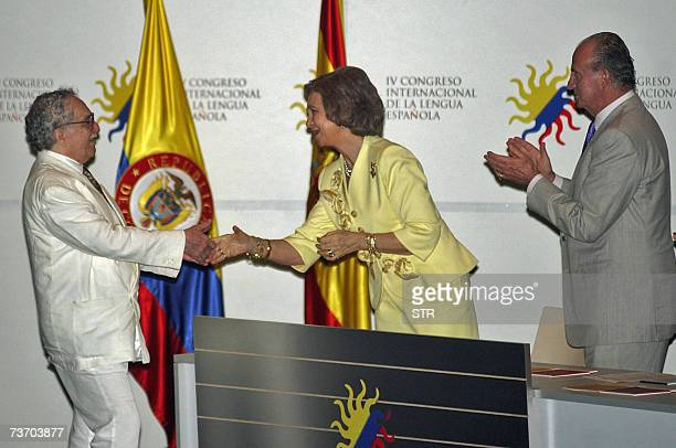 Colombian writer and Nobel Prize Gabriel Garcia Marquez shakes hands with Spain's Queen Sofia as the King Juan Carlos claps during the opening...