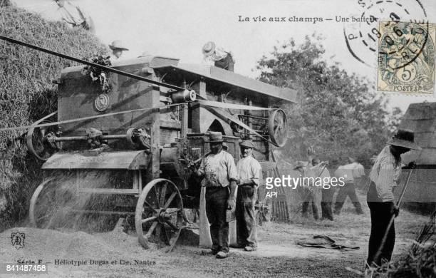 Carte postale illustrée par la photographie d'agriculteurs travaillant avec une batteuse dans un champ en France