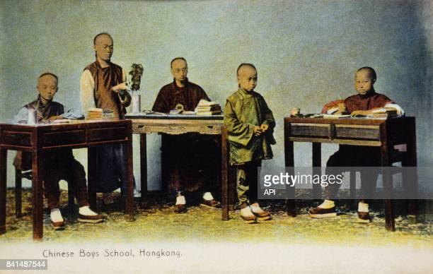 Carte postale illustrée par la photographie d'écoliers chinois à leur bureau à Hong Kong