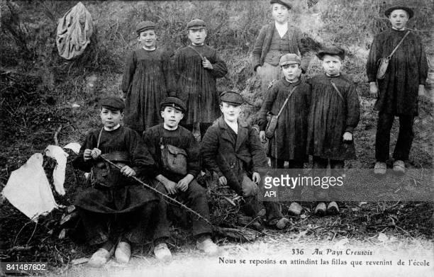Carte postale illustrée par la photographie d'un groupe de jeunes garçons de la Creuse après l'école en France