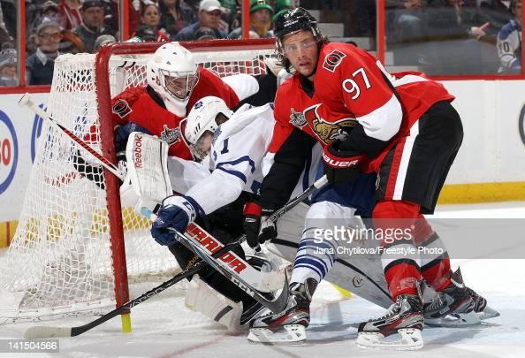Carter Ashton of the Toronto Maple Leafs collides with Ben Bishop of the Ottawa Senators as Matt Gilroy of the Ottawa Senators defends the net during...