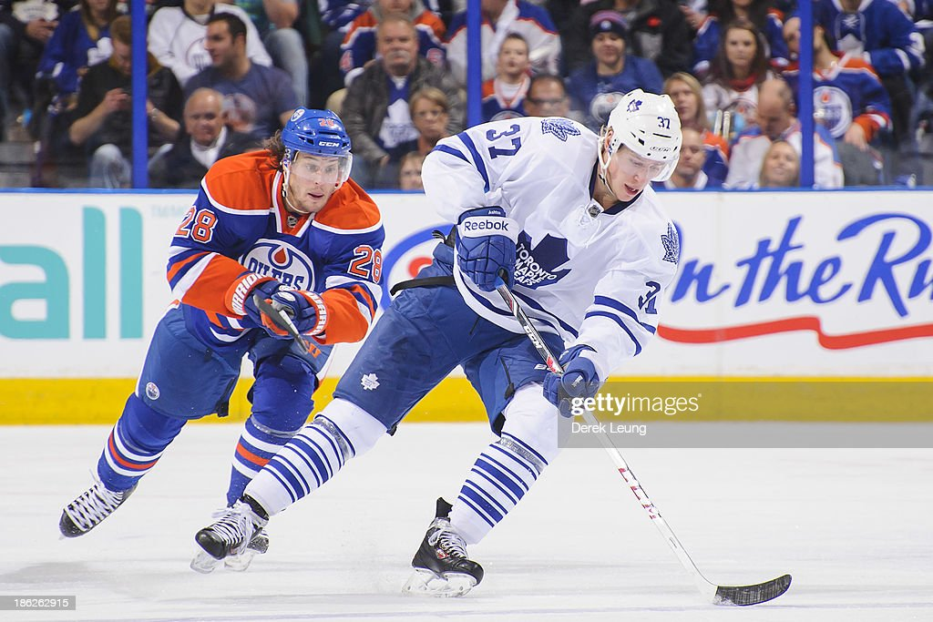 <a gi-track='captionPersonalityLinkClicked' href=/galleries/search?phrase=Carter+Ashton&family=editorial&specificpeople=4779660 ng-click='$event.stopPropagation()'>Carter Ashton</a> #37 of the Toronto Maple Leafs skates with the puck past the defense of Ryan Jones #28 of the Edmonton Oilers during an NHL game on October, 29, 2013 at Rexall Place in Edmonton, AB, Canada.